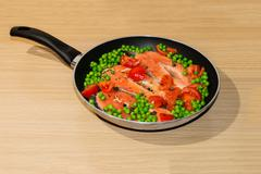Aluminium Pan full of salmon steacks, peas, tomatoes and capers Stock Photos