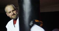 Trainer with a young athlete practicing with a punching bag in slow motion. Stock Footage