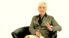 Business middle aged woman sits and talks to camera (interview)-white background Stock Footage