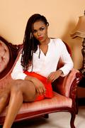 African woman sitting on couch. Stock Photos