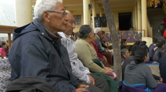 Tibetan devotees listen to a translated speech of the Dalai Lama - stock footage