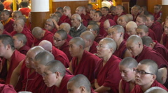 Buddhist monks listen to a speech by the Dalai Lama, politics and religion Stock Footage