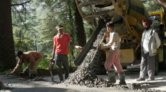Workers dump cement on a new mountain road in Dharamsala, India Stock Footage