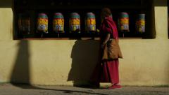 A monk walks past prayer wheels in Dharamsala / McLeod Ganj, India Stock Footage