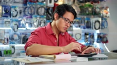 Chinese Man Working In Computer Shop Checking Bills And Invoices - stock footage