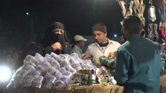 Night market in Hyderabad, veiled Muslim woman shopping, Islam in India Stock Footage