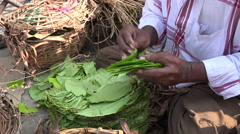 Street vendor folds betel leaves to make paan on a market in Hyderabad, India Stock Footage