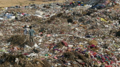 India, two boys play with a kite on a garbage dump Stock Footage