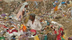 India garbage dump, people search items to recycle, urban scene, poverty - stock footage