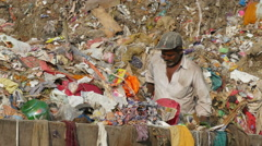 India garbage dump, man collects items to recycle, poverty, wages, income Stock Footage