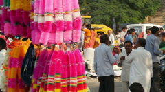 India bazaar, people chat behind vendors selling colorful decoration - stock footage