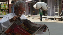 A man reads a newspaper on the streets of Jodhpur, India Stock Footage