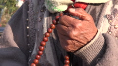 Senior pilgrim uses prayer beads, hands, detail, Kathmandu, Nepal Stock Footage
