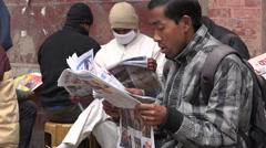Men read newspapers in the streets of Kathmandu, Nepal Stock Footage