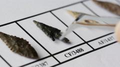 Examining neolithic flint arrowheads, 4K - stock footage