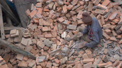 Worker scraping huge pile of bricks, manual labor in Nepal, Asia - stock footage