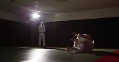 Two young martial arts athletes practice while a trainer assesses their moves. Stock Footage