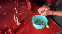 A monk kneads butter for statues in a monastery in Kathmandu Stock Footage