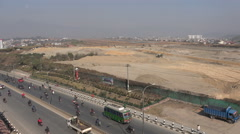 Traffic drives past the runway of Kathmandu International Airport Stock Footage