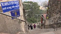 People climb up the Swayambhunath temple complex, warning sign, Nepal Stock Footage