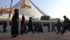 Nepal religion, pilgrims walk around Boudhanath stupa in early morning - stock footage