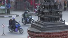 Traffic drives past a miniature temple in Patan, Kathmandu, Nepal Stock Footage