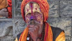 Sadhu smokes marijuana (cannabis) in temple complex in Kathmandu, Nepal Stock Footage