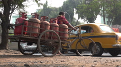 India, Kolkata city, cycle rickshaw rider transports gas cylinders, busy road - stock footage