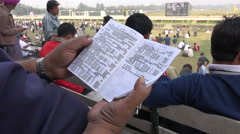 Schedule booklet at Kolkata horse racing track, sports in India - stock footage