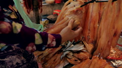 Asian woman hanging on hooks dried fish on the market Stock Footage