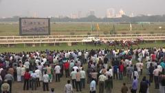 Horse racing tracks, audience, running horses, Kolkata skyline, India Stock Footage