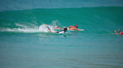 A surfers catches a wave at Nai Harn beach Stock Footage