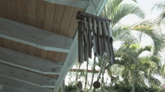 Wind chimes in a sunny day woth palms in the background Stock Footage
