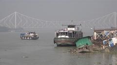 Passengers exit ferry, Howrah bridge, old sunken vessels, Kolkata city, India Stock Footage