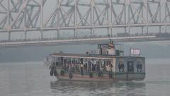 A ferry sails towards the Howrah bridge in Kolkata, India Stock Footage
