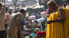 Worker carries many flower bundles at a market in Kolkata, India Stock Footage