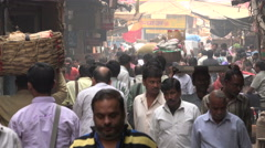 India, people walk through a narrow alley in a busy Kolkata bazaar Stock Footage