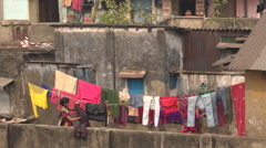 A woman puts clothes on a washing line at a rooftop in Kolkata, India Stock Footage
