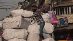 Worker unloading heavy parcels from a cargo truck in Kolkata bazaar, India Stock Footage