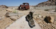 Abandoned Old Truck in Desert Setting with  Old Boots on Rock Track Right Stock Footage
