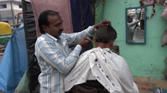 Barber gives a haircut on the roadside in Kolkata, India Stock Footage