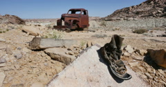 Abandoned Old Truck in Desert Setting with  Old Boots on Rock Locked Stock Footage