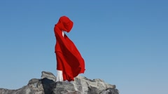 Bride stands on cliff with red flowing fabric Stock Footage