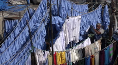 India, ollecting clothing from the washing line in Mumbai's Dhobi Ghats Stock Footage