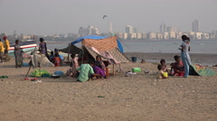 Homeless people live in tents on the beach, Mumbai city skyline, India Stock Footage
