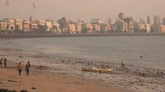 Mumbai city skyline, people visit a polluted Chowpatty Beach Stock Footage