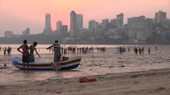 India, Mumbai skyline and Chowpatty Beach, visitors and fishermen - stock footage