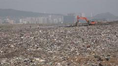 Deonar garbage dumping ground, excavator, people at work, Mumbai, India Stock Footage