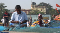India fishing industry, manual labor, men repair nets in Mumbai port Stock Footage