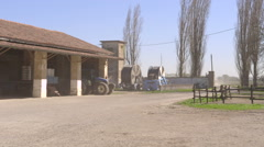 Farmyard with dust moved by the wind and tractor passing by - stock footage